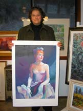 Photo of artist Diane Wallace holding one of her paintings
